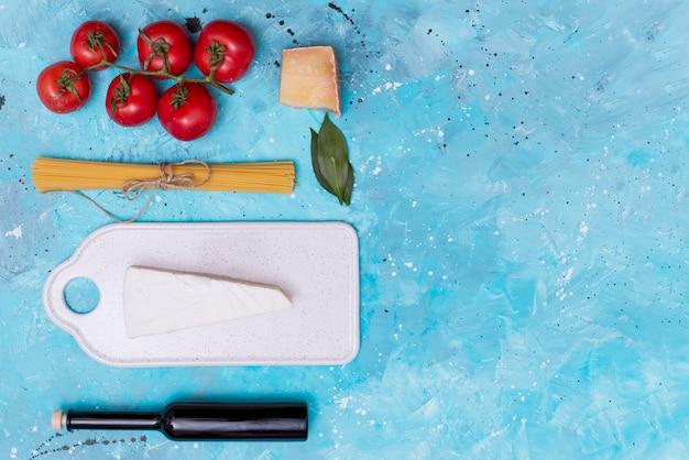 Bando de macarrão espaguete cru e ingrediente saudável com bardo de corte branco sobre fundo azul manchado
