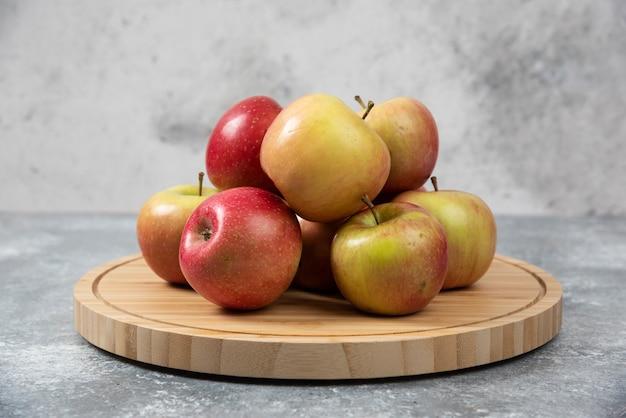 Bando de maçãs frescas maduras colocadas na placa de madeira.