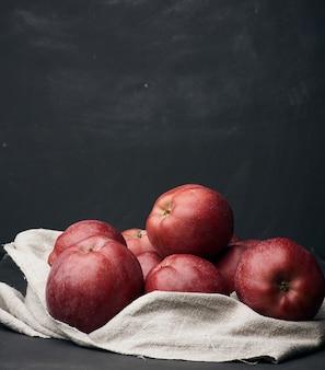 Bando de maçãs maduras vermelhas encontra-se em um guardanapo de linho cinza, fundo preto