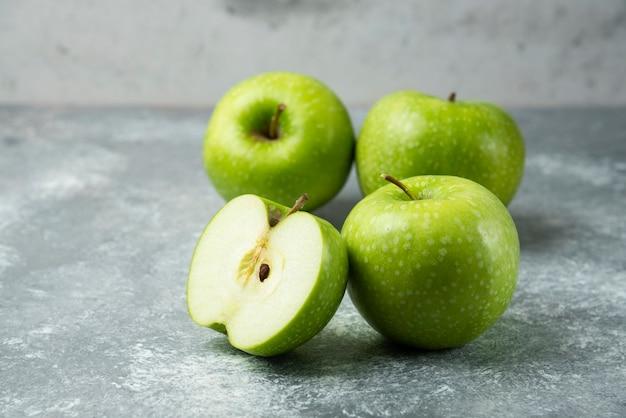 Bando de maçãs verdes em mármore.