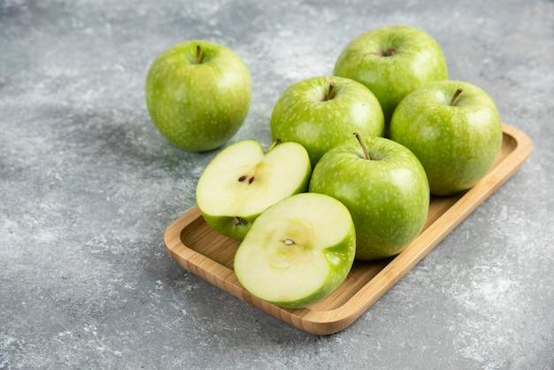 Bando de maçãs verdes inteiras e fatiadas na placa de madeira.