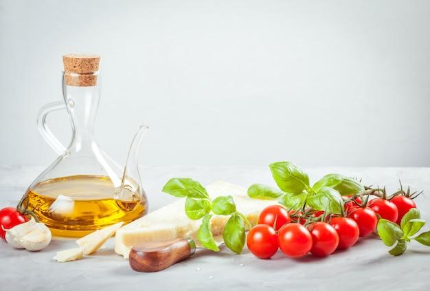 Bando de manjericão fresco, tomate, queijo parmesão, azeite, ingredientes da cozinha italiana