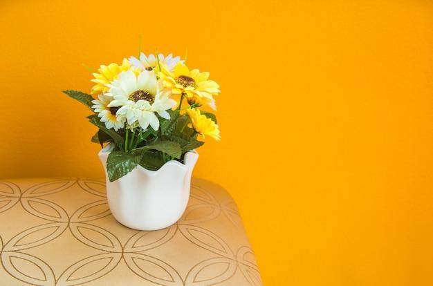 Bando de margarida amarela flores no vaso branco.