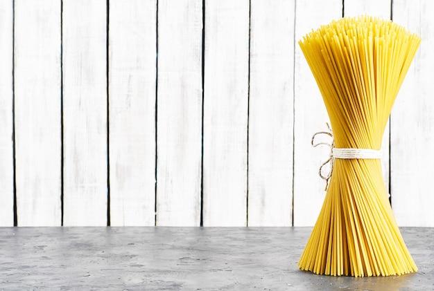 Bando de massa italiana crua. espaguete em um fundo de madeira