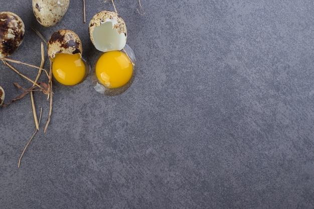 Bando de ovos de codorna crus e gema de ovo na mesa de pedra.