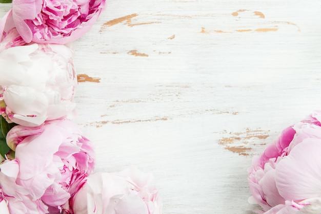 Bando de peônias rosa sobre fundo branco de madeira