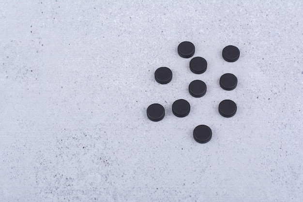 Bando de pílulas pretas sobre fundo de mármore. foto de alta qualidade