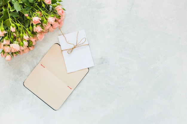 Bando de rosas cor de rosa; envelope e notebook em plano concreto