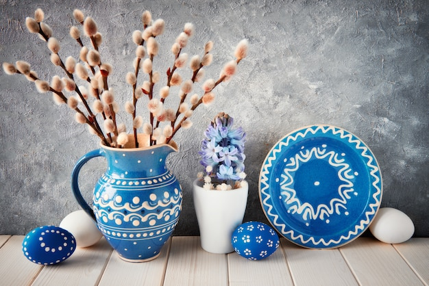 Bando de salgueiro em jarro de cerâmica azul com placa a condizer, ovos de páscoa e decoração de primavera