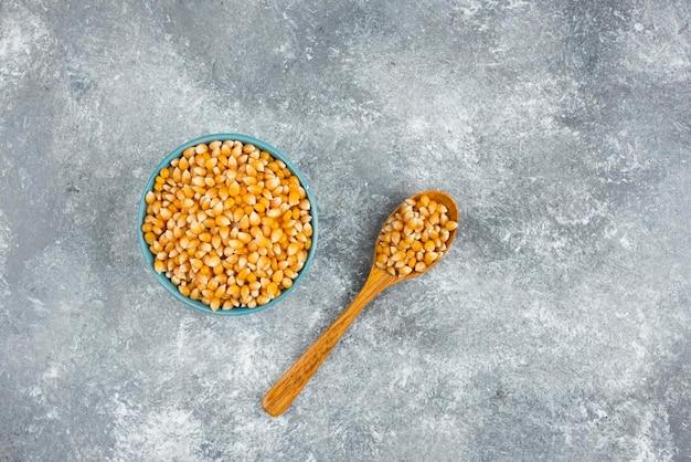 Bando de sementes de milho cru em tigelas azuis e colher de pau.