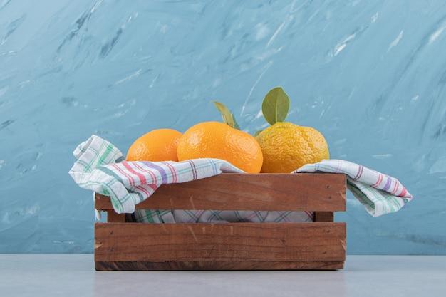 Bando de tangerinas frescas em caixa de madeira. Foto gratuita