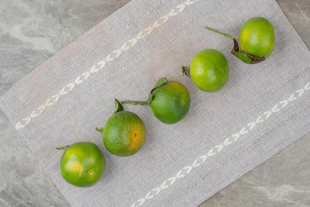 Bando de tangerinas frescas na toalha de mesa cinza.
