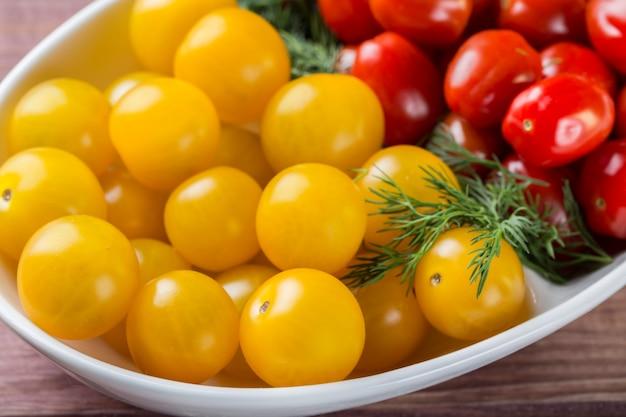 Bando de tomate cereja vermelho e amarelo em uma tigela