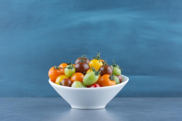 Bando de tomates coloridos em uma tigela branca.