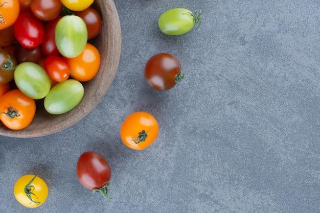 Bando de tomates coloridos em uma tigela de madeira.