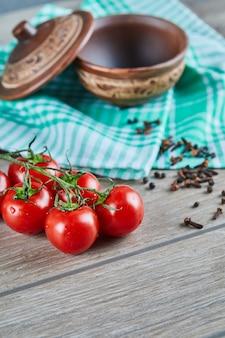 Bando de tomates com ramo e tigela vazia com cravo na mesa de madeira