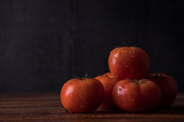 Bando de tomates frescos sobre a mesa de madeira na superfície escura