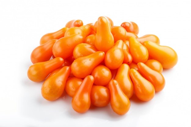 Bando de tomates maduros de uva laranja, isolado no fundo branco