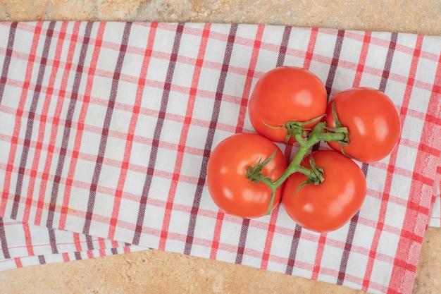 Bando de tomates vermelhos frescos com hastes verdes na toalha de mesa