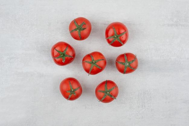 Bando de tomates vermelhos na superfície branca.