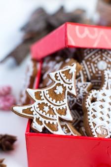 Bando de tradicional natal gingerbread com cobertura em uma caixa de papel vermelho