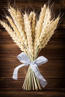 Bando de trigo com uma fita azul em um fundo de madeira.