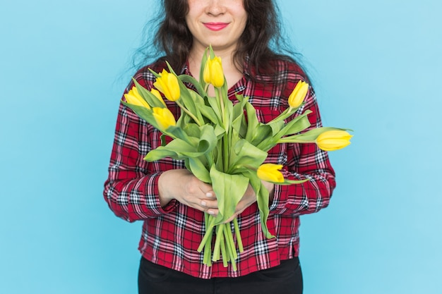Bando de tulipas amarelas nas mãos da mulher na parede azul.