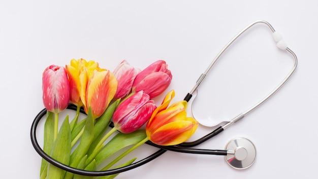 Bando de tulipas cor de rosa e estetoscópio sobre fundo branco. dia nacional do médico. feliz dia da enfermeira.