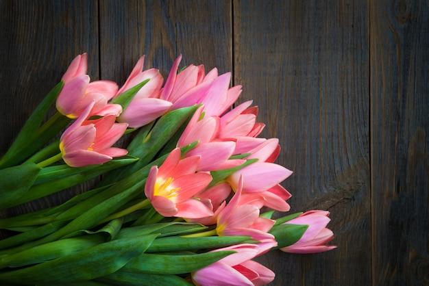 Bando de tulipas cor de rosa no fundo escuro de madeira