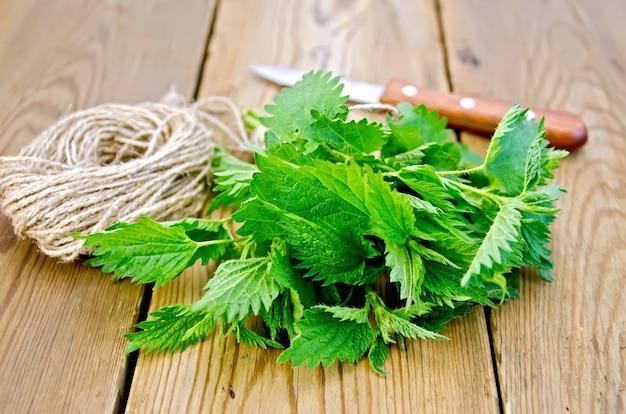 Bando de urtiga verde fresca, faca, bola de barbante em tábuas de madeira