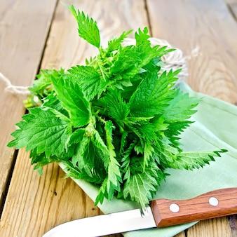 Bando de urtiga verde fresca, uma faca, um novelo de barbante em um guardanapo sobre um fundo de tábuas de madeira