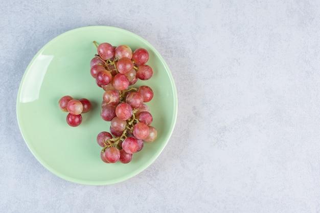 Bando de uva orgânica fresca vermelha na placa verde.