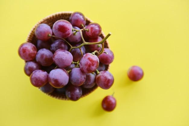 Bando de uva vermelha na cesta - fruta uva fresca na mesa