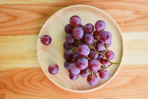 Bando de uva vermelha na placa de madeira sobre uma mesa