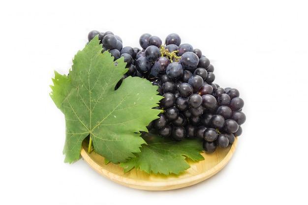 Bando de uvas pretas isolado na placa de madeira e fundo branco com pacote de folha verde