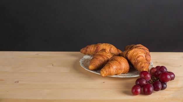 Bando de uvas vermelhas e placa de croissant na mesa contra o fundo preto