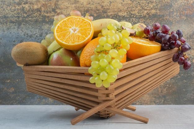 Bando de várias frutas em uma tigela de madeira grande. foto de alta qualidade