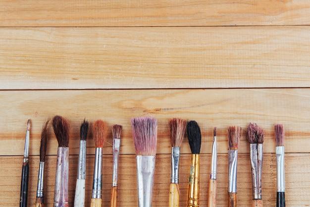 Bando de velhos pincéis de artista na mesa rústica de madeira