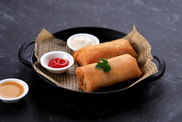 Bandung, indonésia, 02042020: rolinhos primavera fritos, populares como lumpia ou popia. servido em prato de panela preta, mesa de mármore preto. copiar espaço para texto