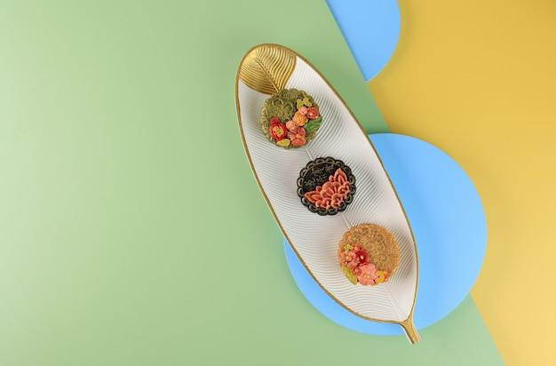 Bandung, indonésia, 02092021: bolo de lua três caseiro (mooncake) sobre fundo amarelo menta. conceito para mid autumn festival com espaço para texto