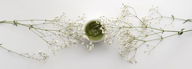 Baner do creme de cara orgânico no recipiente e nas flores brancas na superfície branca. remédio caseiro e conceito de produto de beleza. vista do topo. copie o espaço.
