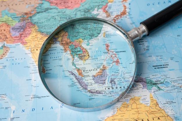 Bangkok, tailândia - 01 de agosto de 2020 ásia, lupa close-up com mapa-múndi colorido