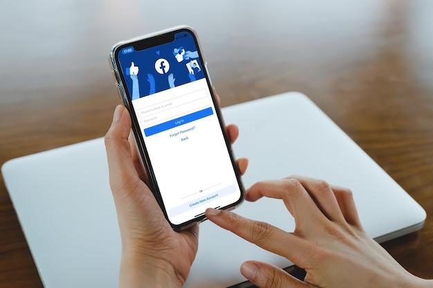 Bangkok. tailândia. 1.2021 de março de 21 logotipo do aplicativo de mídia social do facebook no login, página de registro de inscrição na tela do aplicativo móvel em dispositivos inteligentes do iphone na mão de um empresário no trabalho