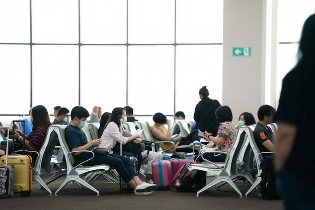 Bangkok, tailândia - 14 de fevereiro de 2020: grupo de turistas usando máscara para se protegerem da covid-19 enquanto usavam telefones e sentavam-se em frente ao portão de embarque