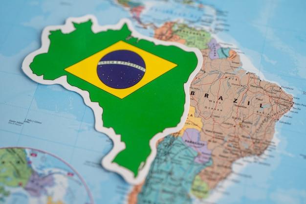 Bangkok, tailândia - 20 de setembro de 2021 bandeira do brasil no fundo do mapa do mundo. bandeira no fundo do mapa do mundo.
