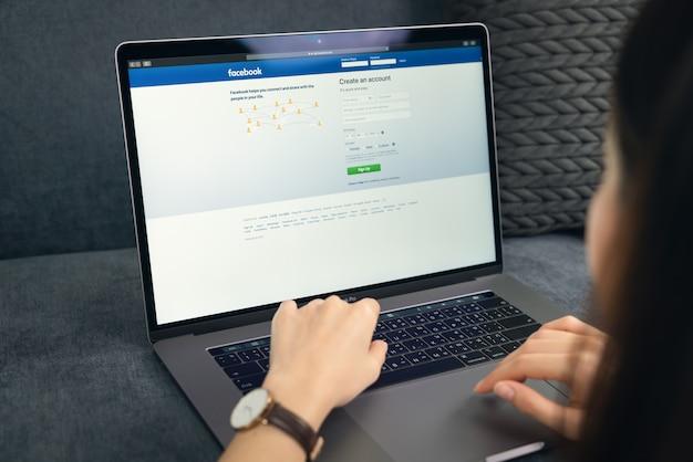 Bangkok, tailândia - 28 de janeiro de 2020: mão de mulher está pressionando a tela do facebook no apple macbook pro, mídias sociais estão usando para compartilhamento de informações e redes.