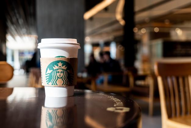 Bangkok, tailândia - 29 de junho de 2018: café de bebida quente da starbucks com suporte em cima da mesa