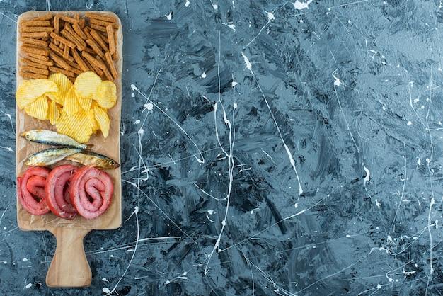 Banha de porco, peixe, batatas fritas e pão ralado em uma placa de corte, sobre o fundo azul.