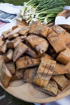 Banha defumada (slanina) em uma placa de madeira. comida tradicional romena.