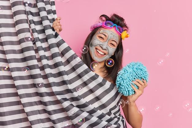 Banhando o conceito de tempo de beleza de frescor. mulher asiática sorridente e positiva inclina a cabeça, tem bom humor, toma banho pela manhã, aplica máscara de argila para a perfeição da pele fica atrás da cortina relaxa no banheiro